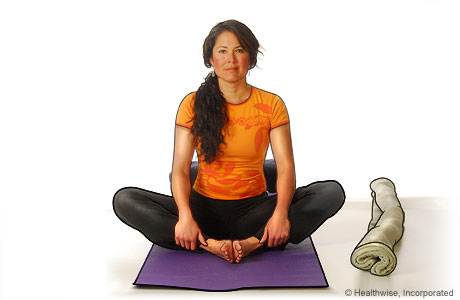 Picture of a woman in step one of reclining bound angle yoga pose
