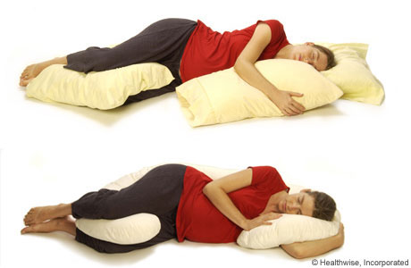 A pregnant woman lying on her side and supported by pillows