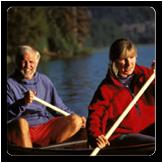 Older couple paddling canoe